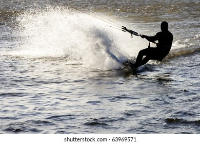 Kite surfer silhouette, sliding fast with a massive spilled water fan, at the Obidos lagoon, Bom Sucesso, Foz do Arelho, Silver Coast, Portugal