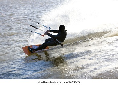Kite surfer sliding fast with a massive drag water fan, at the Obidos lagoon, Bom Sucesso, Foz do Arelho, Silver Coast, Portugal
