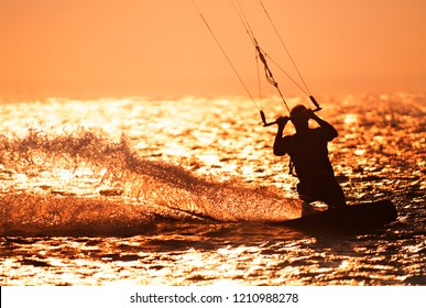 Kite Surfer surfing waves, silhouetted againtst setting sun