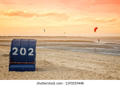 Kite surfing at the beach of Hooksiel, German North Sea coast, beach chair in foreground