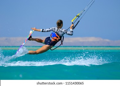 Kite surfing girl in sexy swimsuit with kite in sky on board in blue sea riding waves with water splash. Recreational activity, water sports, action, hobby and fun in summer time. Kiteboarding sport