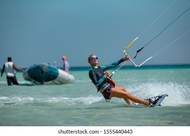 Kite surfing girl in sexy swimsuit with blue kite. Recreational activity, water sports, action, hobby and fun in summer time.