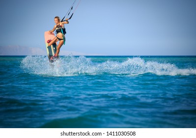 Kite surfing girl in swimsuit with kite in sky on board in blue sea riding waves with water splash. Recreational activity, water sports, action, hobby and fun in summer time. Kiteboarding sport