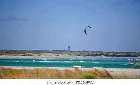 Kite surfing in strong southerly winds,  these Surfers need them for good rides. Wind Surfers out in the surf, at the mouth of the Blackwood River, Augusta.
