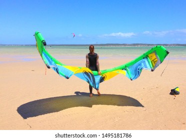Kite surfing young woman or girl holding kite at beach ready to go kiting. Kite boarding sport, water sport, action, freedom, hobby and holiday summer fun. Young woman riding waves with kite.