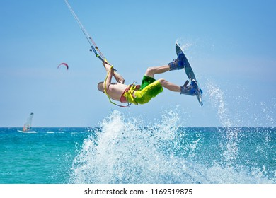 kiteboarder athlete kitesurfing and performing jumping tricks