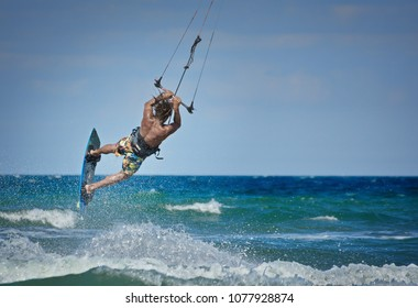 Kiteboarder athlete performing kiteboarding jumping tricks on the water in the sea