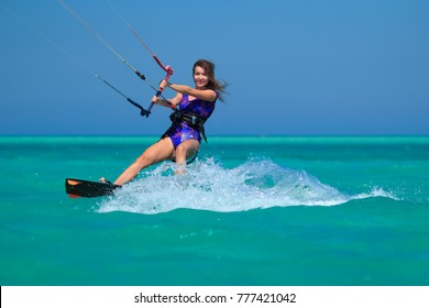 Kiteboarding girl in short bikini on a kite board riding in the blue water of the Red Sea, Egypt, Africa. Active water recreational sport, hobby and fun during vacation. Kitesurfing sports activities