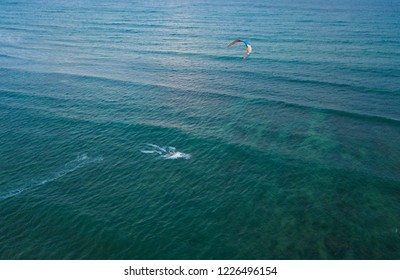 Kiteboarding, kite surf. Extreme sport kitesurfing in tropical blue ocean, clear beach. Aerial views, top view of kitesurfing on the waves of the beautiful sea in Vietnam. Kite surfer rides the waves