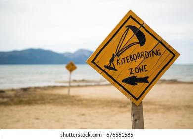 Kiteboarding sign, wooden kitesurfing signpost on a beach at adriatic sea in Croatia. Inspiring kitesurfer silhouette, sport and recreation concept.