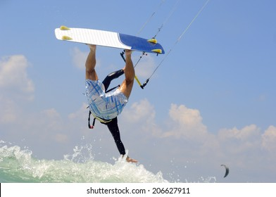 Kiteboarding in  a sunny summer day on  a Mediterranean sea coast