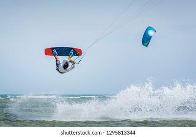 kitesurfer athlete performing kitesurfing jump and unhooked kiteboarding tricks