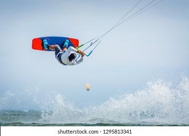 kitesurfer athlete performing kitesurfing trick and jump while kiteboarding