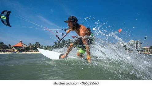 Kitesurfer with board on ocean wave