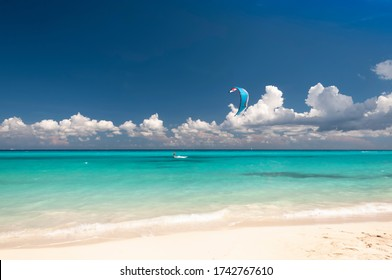 Kitesurfer Caucasian man with Kiteboard in front of an amazing and deserted tropical beach, on the horizon the blue sky and white clouds