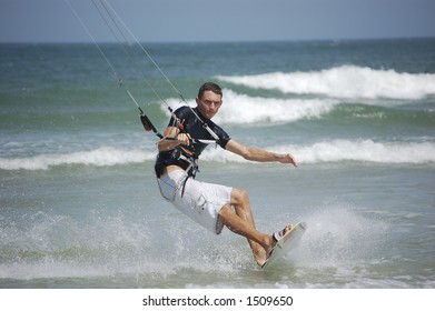 A kitesurfer concentrates on precise balance as he approaches the beach at Ponce Inlet Beach, Florida