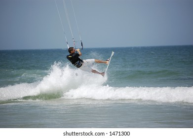 A kitesurfer launches into the air off a breaker at Ponce Inlet Beach, Florida