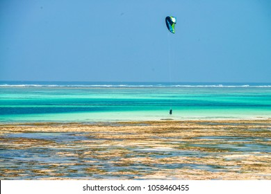 Kitesurfer at low tide on beach in Zanzibar