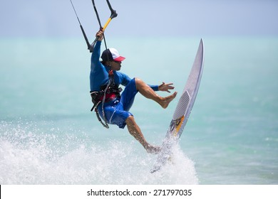 A kitesurfer performing an aerial trick riding strapless surfboard on a sunny day.