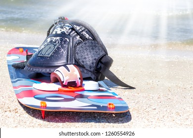 Kitesurfer prepating his equipment on the beach. trapezium and board at sunny day