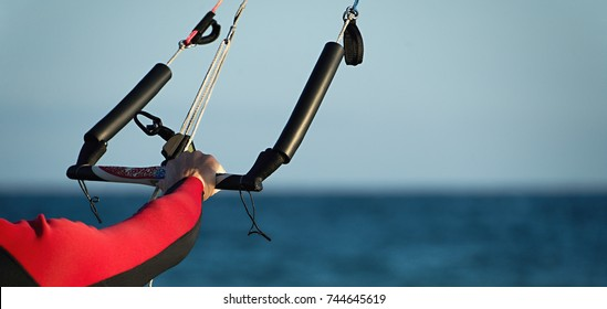 Kitesurfer ready for kitesurfing rides in blue sea detail control bar