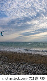 kitesurfer rides a kite-surf on waves of the sea in a small storm on a summer day