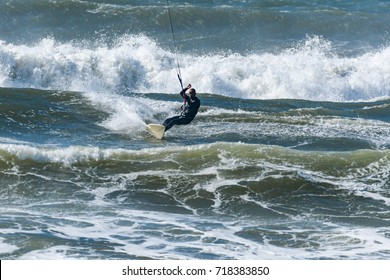 Kitesurfer riding ocean waves on a bright sunny day.