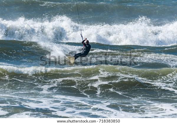 Kitesurfer riding ocean waves on a bright sunny day.