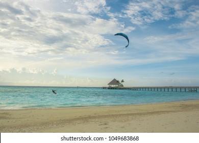 A kitesurfer surfs near the beach near a resort in Maldives