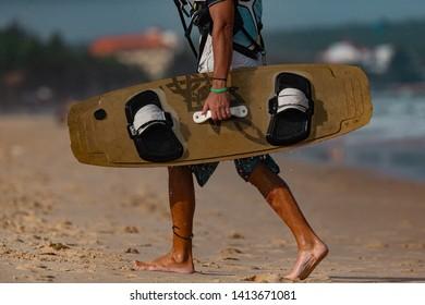 Kitesurfer walks on the beach of the sea in Mui Ne, Phan Thiet, Binh Thuan, Vietnam. Kitesurfer torso with Kiteboard  In Action