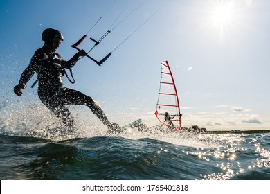 Kitesurfer and windsurfer having fun on the water while backlit from the sun