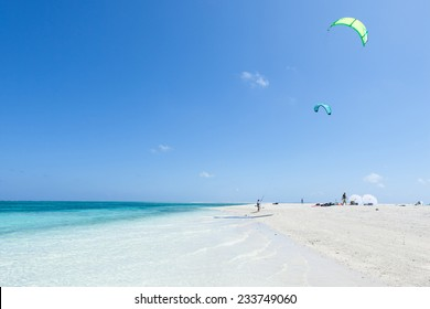 Kitesurfers preparing on coral sand cay beach with clear tropical water, Kume Island, Okinawa, Japan