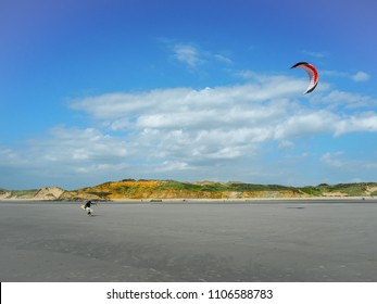 Kitesurfers walking back to the beach at Pointe aux oies coastline near Wimereux in the French Opal coast, famous for kitesurfing