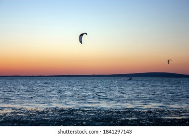 Kitesurfing against the sky at sunset. Riding the waves. Kites in the sky above the sea.