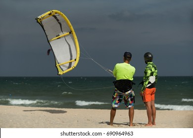 Kitesurfing instructor and male student in sea waters man trying to lift kite