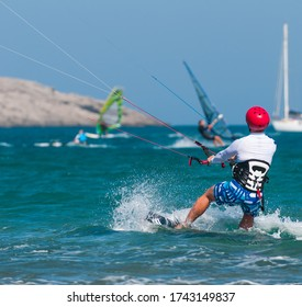 Kitesurfing Kiteboarding action photo of a surfer among other athletes in   the mediterranean sea.