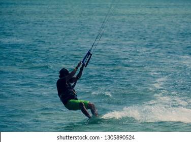Kitesurfing, kiteboarding, kite surf. Extreme sport kitesurfing in tropical blue ocean, clear beach. Stock photo image of kitesurfing on the waves of the beautiful sea in Vietnam. Kite surfer