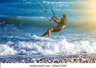 Kitesurfing. Kitesurfer rides the waves on high speed at sunset