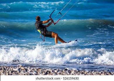 Kitesurfing. Kitesurfer rides the waves on high speed at the sunset