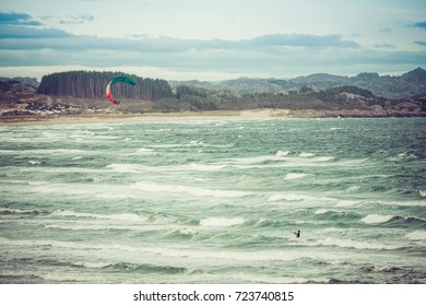 Kitesurfing man in action on stormy sunset evening at Brusand Beach, Norway.