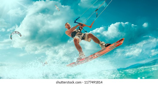 Kitesurfing. Man rides on kite on waves