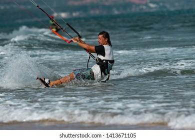Kitesurfing on the waves of the sea in Mui Ne beach, Phan Thiet, Binh Thuan, Vietnam. Kitesurfing, Kiteboarding action photosKitesurfer In Action