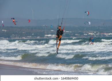Kitesurfing on the waves of the sea in Mui Ne beach, Phan Thiet, Binh Thuan, Vietnam. Kitesurfing, Kiteboarding action photos Kitesurfer In action