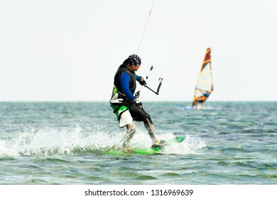 Kitesurfing and windsurfing action photos. Man rides a kite on windsurfer background. Selected focus