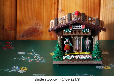 kitsch weather house with a barometer and figurines in traditional alpine dresses