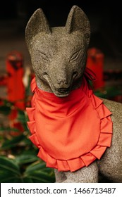 Kitsune Japanese Fox statue with red apron at Shinto shrine - Close up face details - Japan god guard fox