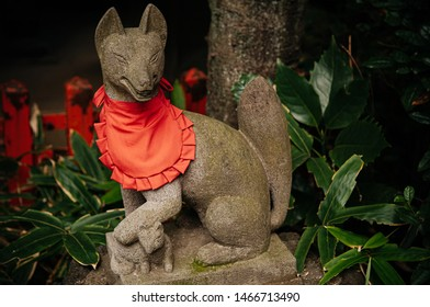 Kitsune Japanese Fox statue with red apron at Shinto shrine - Close up details - Japan god guard fox
