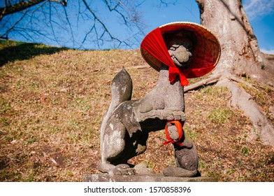 Kitsune Japanese Fox stone statue with red scarft and hat at shrine of Aizu Wakamatsu Tsuruga castle - Close up face details - Japan god guard fox