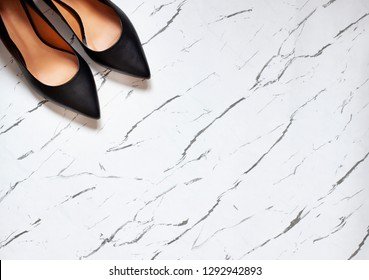 Kitten heel court shoes on the white marble background. Top view. Copy space