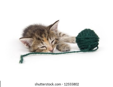 A kitten takes a nap while holding a green ball of yarn on a white background. One in a series